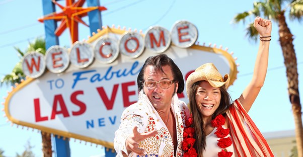 elvis and a woman celebrate their wedding in front of the famous welcome to las vegas sign