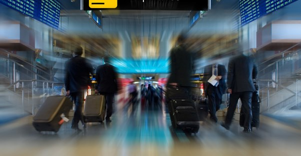 a departure gate with business class passengers walking toward the airline gates