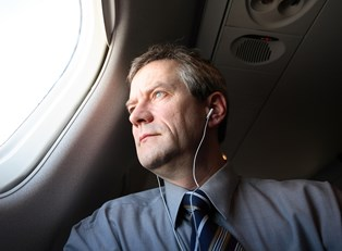 a business man gazes out of a business class airplane window while listening to music through headphones