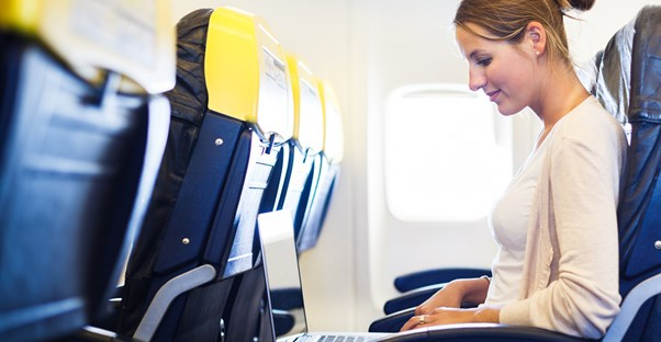a woman sits in economy class typing on her laptop