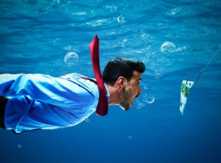 a business man underwater is being tempted by money on the end of a fishing line