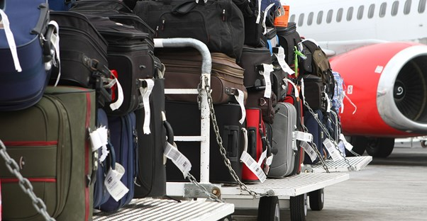 a pile of luggage waits to be loaded into the cargo hold of an airplane