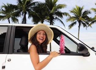 a young woman enjoys the road in her newly rented car