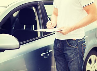 a car rental worker inspects a newly returned car
