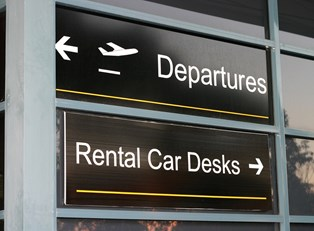 an airport sign pointing the way to the rental car desks