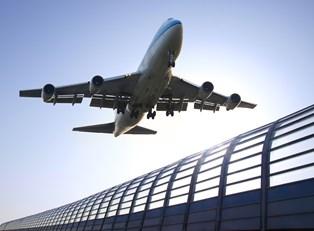a airplane flies over an air terminal