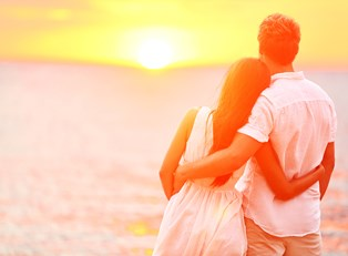 a couple embraces in front of a sunset