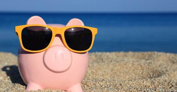 a piggy bank with sunglasses on the beach