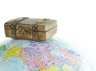 a suitcase, ready to travel, sits on top of a globe