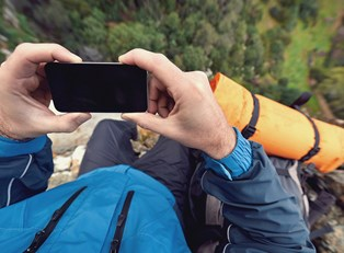 a hiker uses an app to determine a location on a map