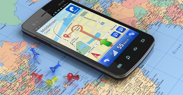 a GPS app sits open on a cell phone which lies on top of a map