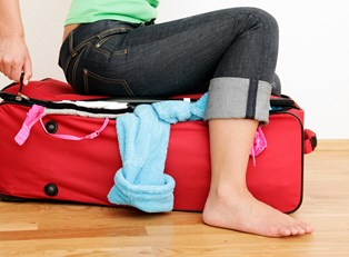 a traveler sits on her overflowing suitcase forcing it closed