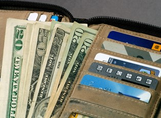 a travel wallet overflows with cash and credit cards