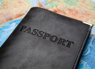 a passport travel wallet lies upon a map